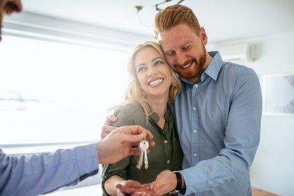 Schlüsselübergabe vom Immobilienmakler an neue Mieter