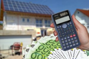 Haus mit Taschenrechner und Geld zur Berechnung der Grundsteuer