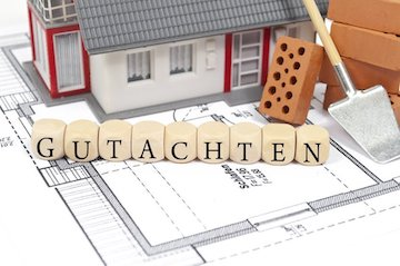 Haus-Modell mit Grundriss und dem Wort Gutachten